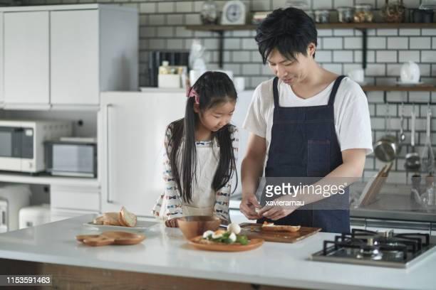 日本の父は若い娘と一緒に昼食を準備します - 料理 ストックフォトと画像