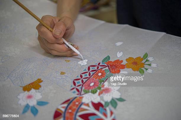 Japanese female artisan has a painting of the kimono