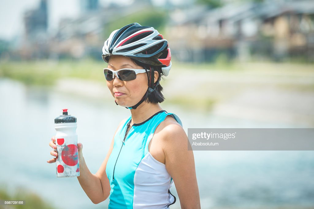 Japanese Female Bicycle Rider Drinking Water By Kamo River