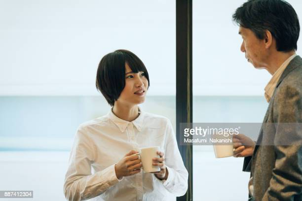 Japanese female businessman receiving advice from his boss
