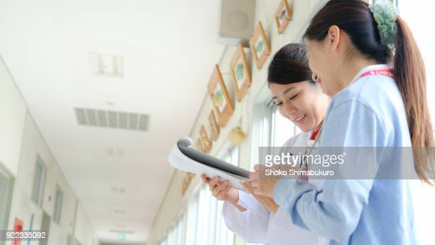 A Japanese female doctor and a nurse. Meeting while looking at the chart in the hallway.