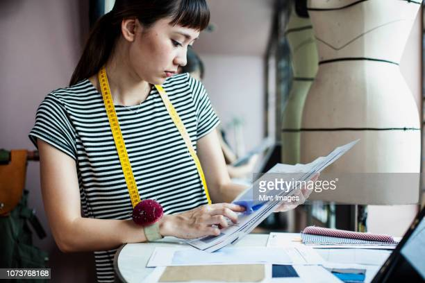 Japanese female fashion designer working in her studio, looking at fabric samples.