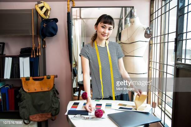 japanese female fashion designer working in her studio, smiling at camera. - デザイナー ストックフォトと画像