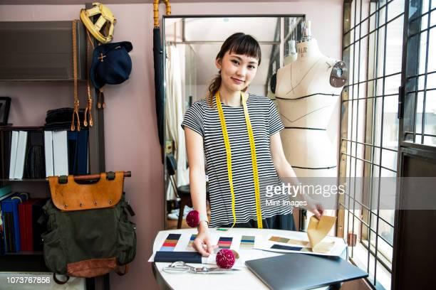 japanese female fashion designer working in her studio, smiling at camera. - design professional ストックフォトと画像