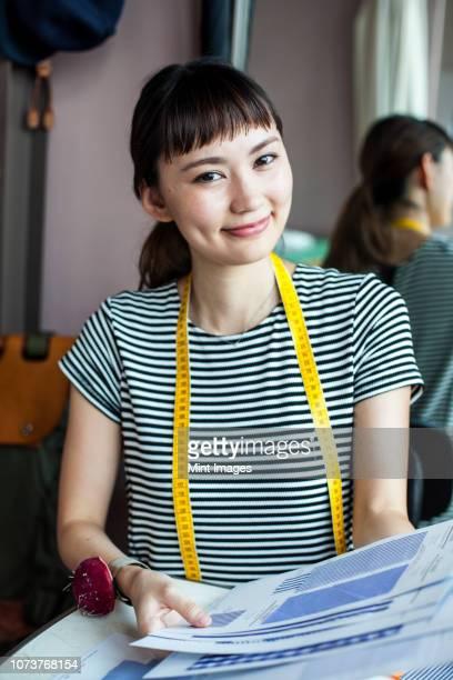 japanese female fashion designer working in her studio, smiling at camera. - ポニーテール ストックフォトと画像