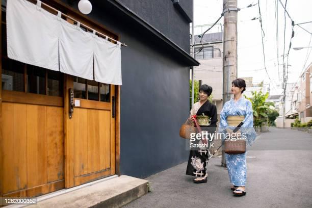 浴衣の日本人女性の友人が日本の伝統的な「旅館」ホテルに入る - のれん ストックフォトと画像