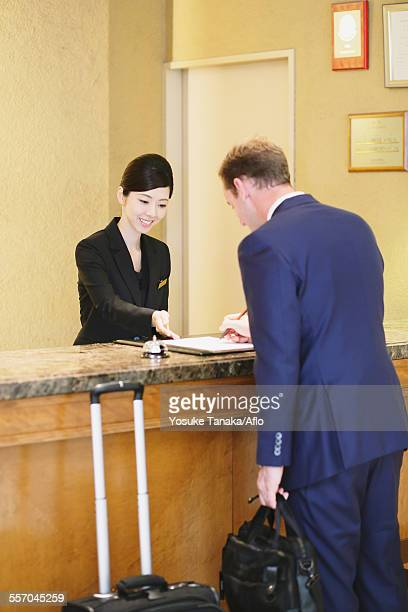 Japanese female hotel concierge dealing with a customer