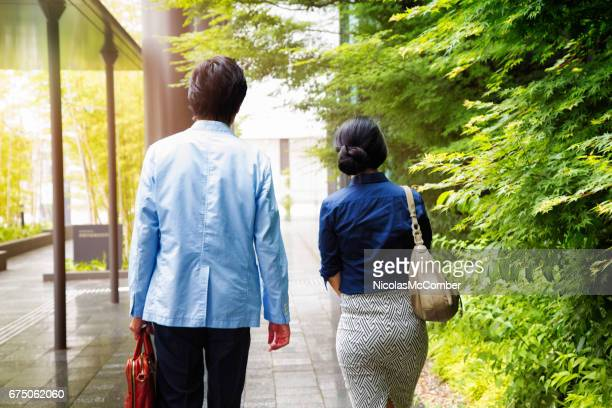 Japanese Female office worker with male colleague walking to work