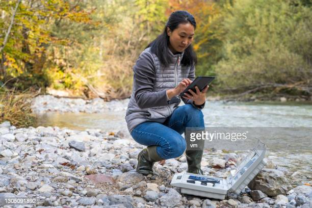 japanese female researcher testing water quality in nature. woman using wireless digital tablet. - biologist stock pictures, royalty-free photos & images