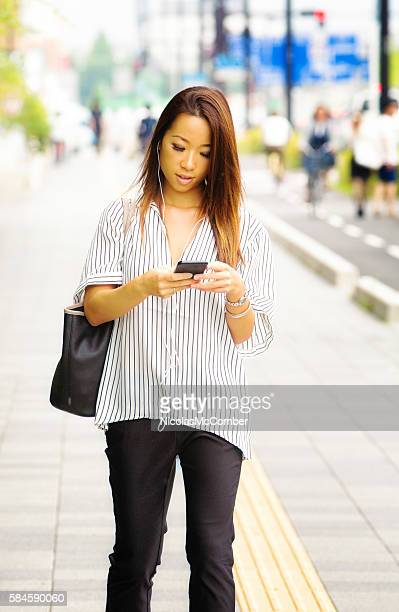Japanese female stops commute to play game on mobile phone