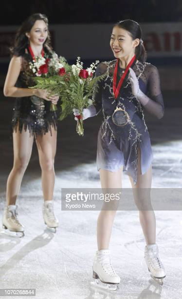 Japanese figure skater Rika Kihira waves to fans after winning the women's Grand Prix Final in Vancouver Canada on Dec 8 2018 Seen in the back is...