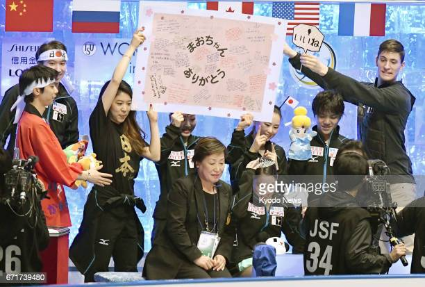 Japanese figure skaters hold up a board bearing messages of respect and gratitude to Mao Asada a threetime world figure skating champion and silver...