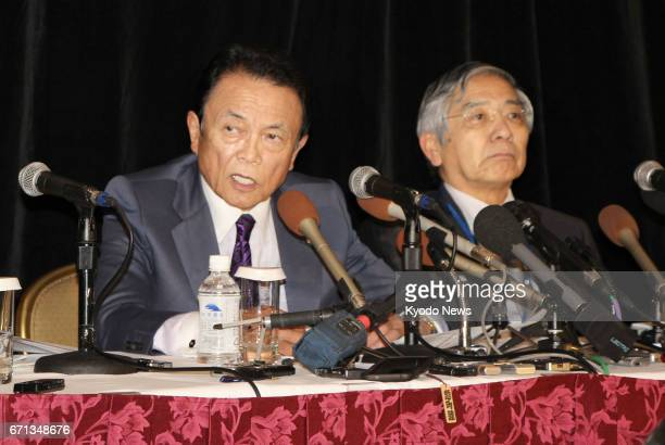 Japanese Finance Minister Taro Aso and Bank of Japan Governor Haruhiko Kuroda attend a press conference on April 21 in Washington following a meeting...