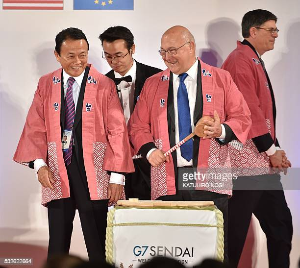 Japanese Finance Minister Taro Aso chats with France's Minister of Finance and Public Accounts Michel Sapin during a welcome reception hosted by the...
