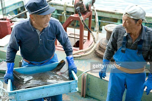Japanese fishermen carrying crate of flounder