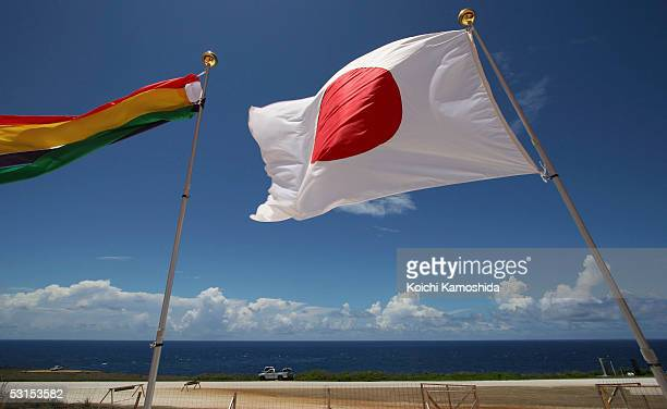 Japanese flag flies on a temple close to a monument to the hundreds of Japanese civilians and soldiers who jumped off Banzai Cliff to their deaths to...