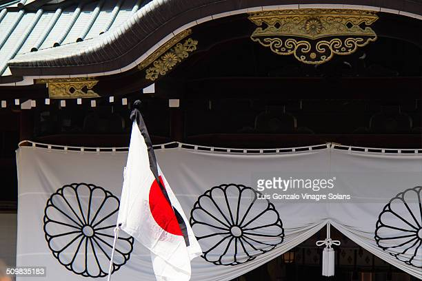 Japanese flag with black mourning ribbon on 15th August world war 2 surrender anniversary at the Yasukuni shrine in Tokyo Japan