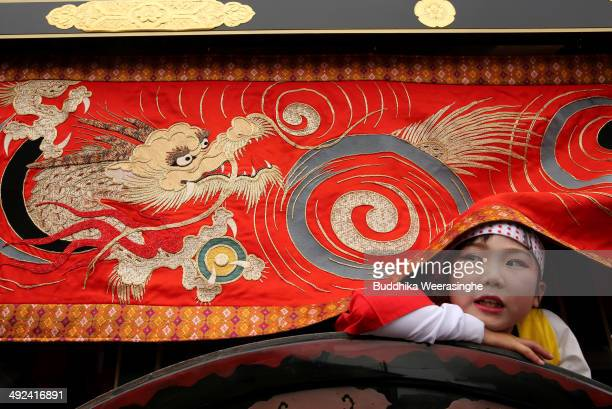 Japanese flower cart girl looks under the dragon banner during the Mikuini annual festival on May 20 2014 in Sakai Japan The annual festival takes...