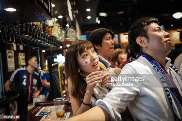 A man celebrates holding a samurai blue scarf as Japanese fans gather in around Shibuya crossing after the Japan National Team's victory against...