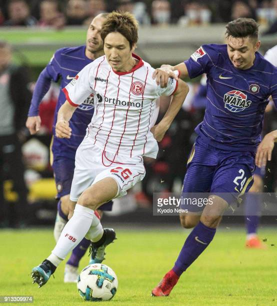 Japanese football player Genki Haraguchi of Fortuna Dusseldorf tries to defend the ball against JohnPatrick Strauss of Aue during a match in...