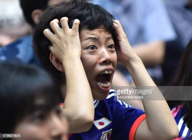 A Japanese football supporter reacts as she attends a public screening in Tokyo on July 6 of the 2015 FIFA Women's World Cup final between Japan and...
