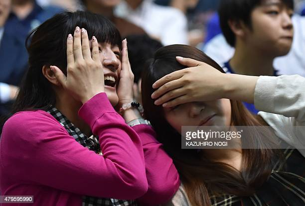 Japanese football supporters react following a goal by the US as they attend a public screening in Tokyo on July 6 of the 2015 FIFA Women's World Cup...