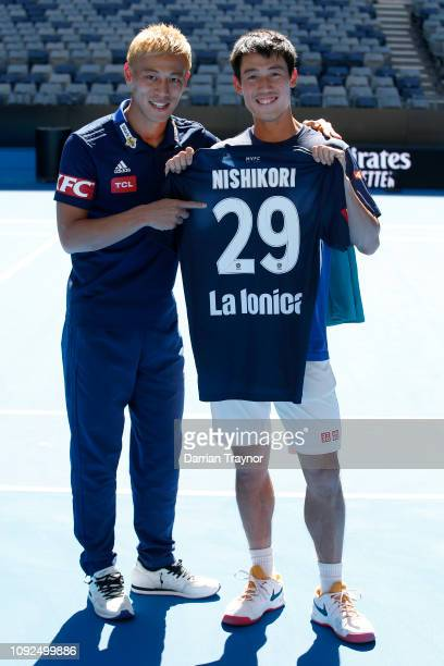 Japanese footballer and Melbourne Victory player Keisuke Honda meets Kei Nishikori during a practice session ahead of the 2019 Australian Open at...