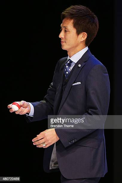Japanese footballer Takashi Fukunishi holds a ball containing a teams name drawn from a pot on stage during the final draw for the 2015 AFC Asian Cup...