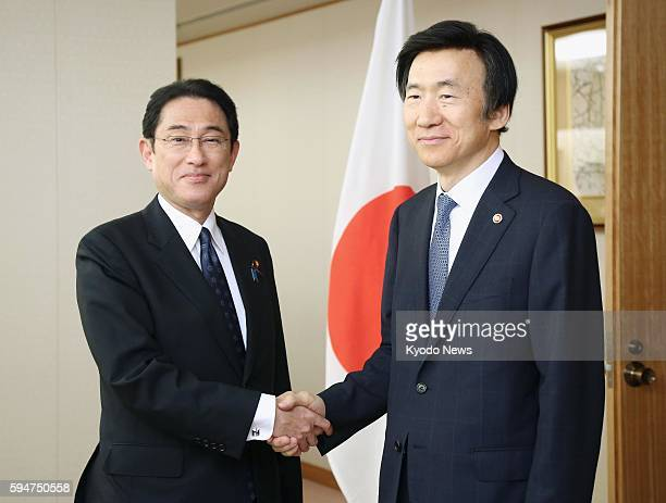 Japanese Foreign Minister Fumio Kishida and his South Korean counterpart Yun Byung Se shake hands ahead of their talks at the Foreign Ministry in...
