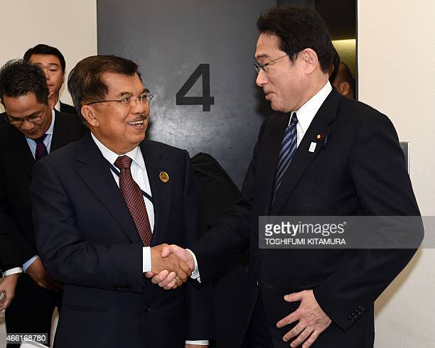 Japanese Foreign Minister Fumio Kishida greets Indonesian Vice President Jusuf Kalla during their bilateral meeting while attending the third UN...