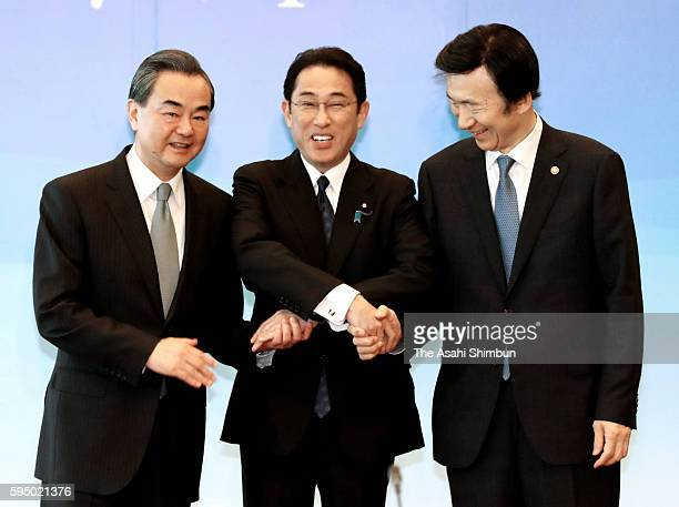 Japanese Foreign Minister Fumio Kishida , his Chinese counterpart Wang Yi and South Korea's Yun Byung-se shake hands at the start of their trilateral...