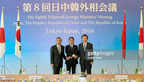 Japanese Foreign Minister Fumio Kishida joins hands with his Chinese counterpart Wang Yi and South Korean counterpart Yun Byung Se at the start of...