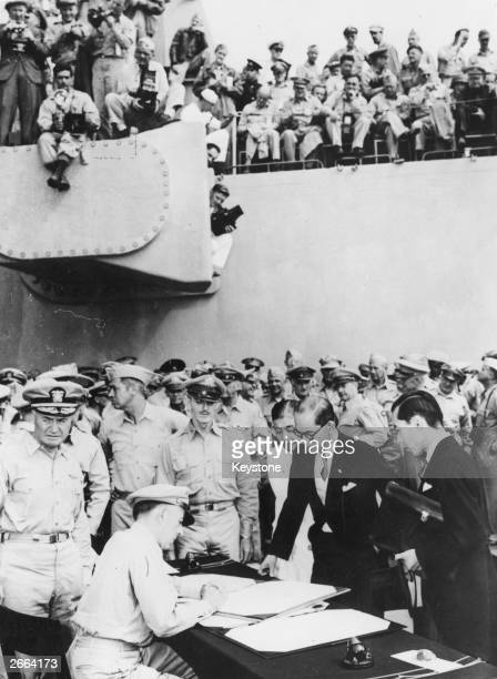 Japanese Foreign Minister, Mamoru Shigemitsu discussing surrender documents with Lt General Richard K Sutherland , Rear Admiral Forrest Sherman is...