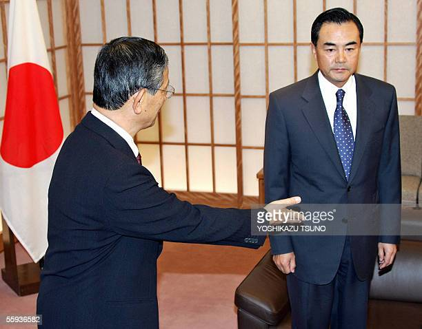 Japanese Foreign Minister Nobutaka Machimura greets Chinese ambassador to Japan Wang Yi for their meeting at Machimura's office in Tokyo 17 October...