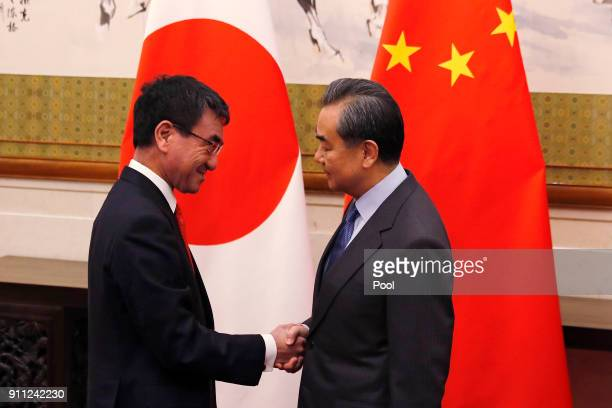 Japanese Foreign Minister Taro Kono left shakes hands with Chinese counterpart Wang Yi before their meeting at the Diaoyutai State Guesthouse on...