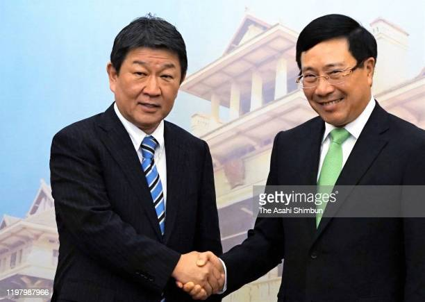 Japanese Foreign Minister Toshimitsu Motegi and Vietnamese Foreign Minister Pham Binh Minh shake hands during their meeting during their meeting on...