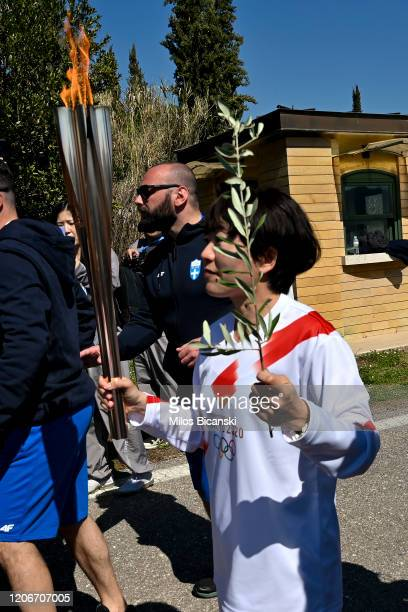 Japanese former marathon runner Noguchi Mizuki carries the torch and the olive branch during the opening of the Olympic flame torch relay for the...