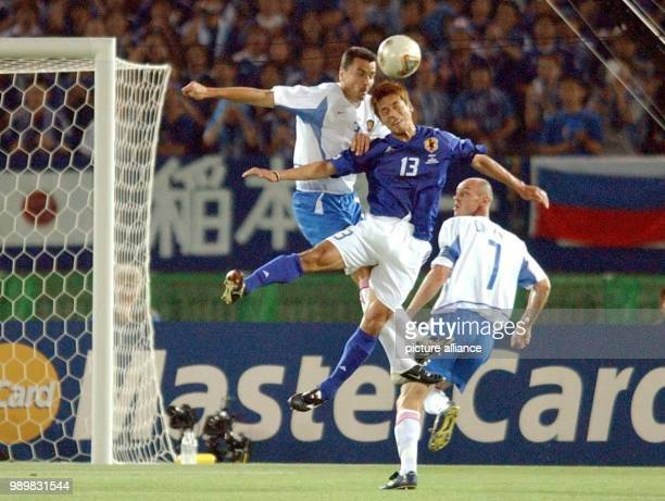 Japanese forward Atsushi Yanagisawa jumps up and manages a header in a struggle for the ball with Russians midfielder Andrej Solomatin and defender...