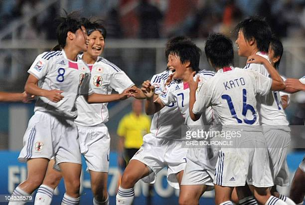 Japanese forward Kumi Yokoyama is surrounded by teammates after scoring the team's second goal during the FIFA Women's Under17 semifinal match on...