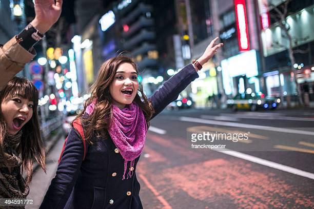 Amigos a ligar o táxi japonês em Tóquio