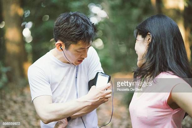 japanese friends checking data on smartphone while doing sport outdoors - lypsekyo16 stock pictures, royalty-free photos & images