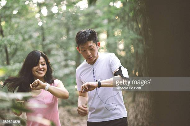 Japanese friends checking data on smartwatch while doing sport outdoors