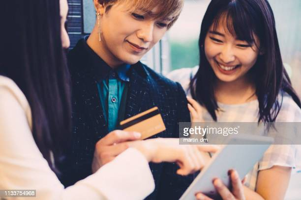 japanese friends making an online hotel reservation - lypsekyo16 stock pictures, royalty-free photos & images