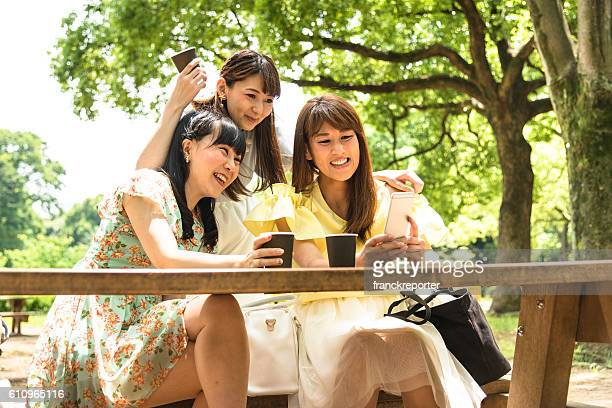 japanese friends take a selfie on the park