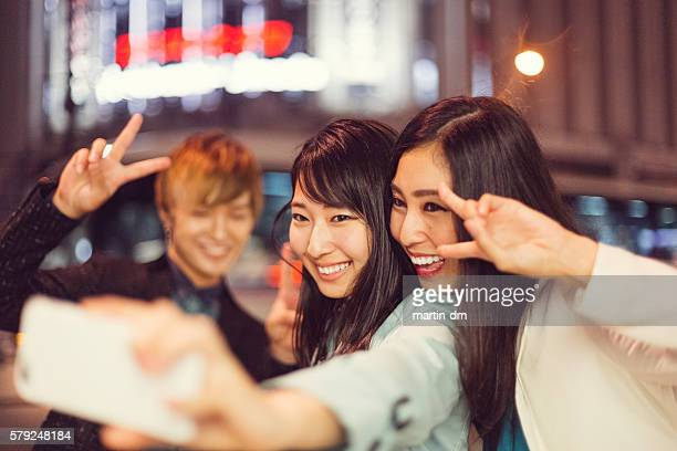 Japanese friends taking selfie at the street