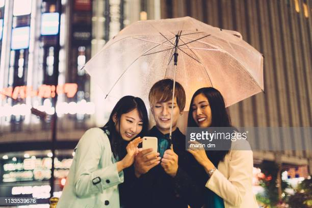 japanese friends using smartphone outside on rainy day - surfing the net stock pictures, royalty-free photos & images