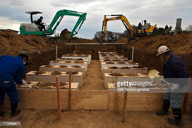 Japanese funeral parlor workers shovel dirt onto coffins containing unidentified earthquake victims during a mass funeral on April 8 2011 in Yamamoto...