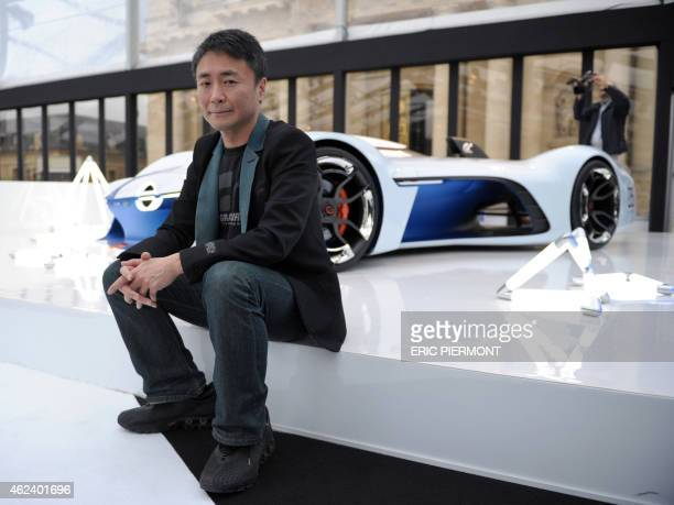 Japanese game designer and creator of the video game Gran Turismo Kazunori Yamauchi poses in front of the Vision Gran Turismo concept car developed...