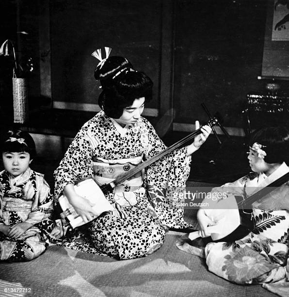 A Japanese Geisha girl teaches two children the art of playing the samisen a traditional stringed instrument