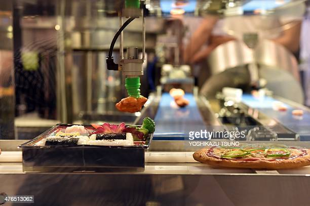 Japanese giant Kawasaki Heavy Industries robot machinery packs lunches and makes pizzas during a cooking demonstration at the International Food...